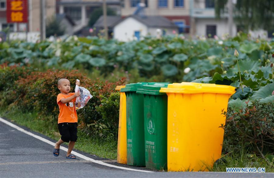A child prepares to put trash into a classified garbage bin at Gangkou Village of Anji County, east China\'s Zhejiang Province, Aug. 16, 2018. As \
