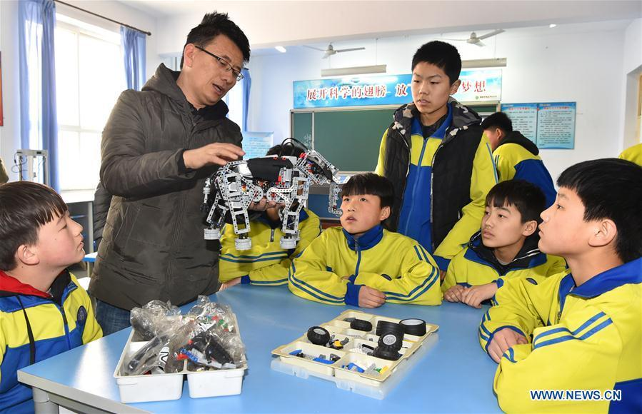 A teacher shows students how to assemble a model in Hanjiawa Middle School of Gaocheng District, Shijiazhuang City, north China\'s Hebei Province, Feb. 28, 2019. A series of activities including dancing, model-assembling and calligraphy have enriched children\'s extra-curricular life and guaranteed their all-round development. (Xinhua/Zhang Xiaofeng)