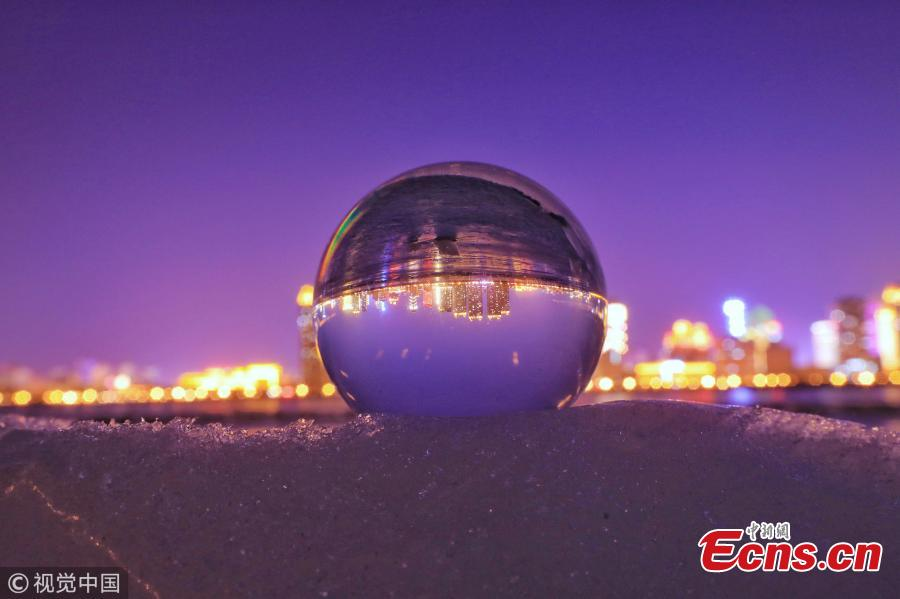 Refraction photography using a crystal ball on ice shows a view of the landscape near the Songhua River in Harbin City, Heilongjiang Province, March 4, 2019. (Photo/VCG)