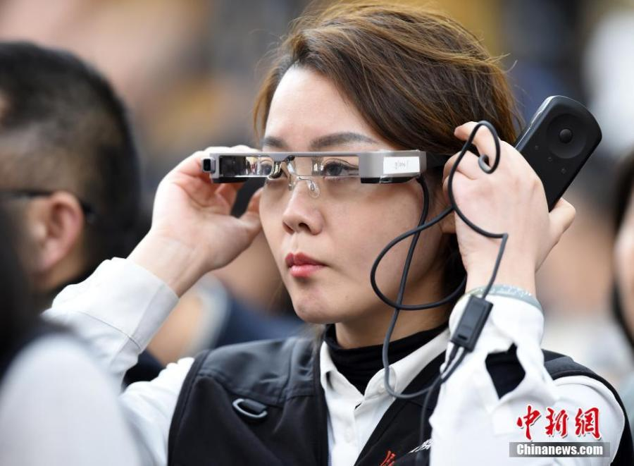 A reporter wears virtual reality (VR) glasses while covering the second session of the 13th National People\'s Congress at the Great Hall of the People in Beijing on Tuesday, March 5, 2019. The VR glasses can record the voice of the wearer, and the tiny camera installed on the frame of the glasses can capture high-definition videos. (Photo/China News Service)