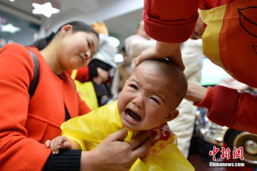 A child gets a haircut at a barbershop in Baokang County, Central China\'s Hubei Province, March 8, 2019. March 8 marks traditional Chinese festival Long Tai Tou (dragon head raising), which refers to the start of spring and farming. During the festival, held on the second day of the second month of the lunar calendar, people play dragon lanterns, eat noodles, shave their hair, and pray for luck.(Photo: China News Service/Yang Tao)
