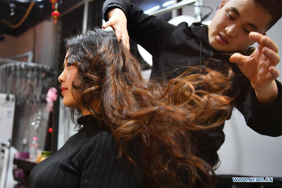 A woman has her hair done at a barber shop in Tianshui, northwest China\'s Gansu Province, March 5, 2019. Along with China\'s reform and opening-up starting from 1978, Chinese women have refreshed their images year after year, which can be simply seen from their hairstyles. Women\'s hairstyles, just like a mirror, reflect fashion changes and most importantly, Chinese women\'s increasingly diversified definition of beauty. (Xinhua/Chen Bin)