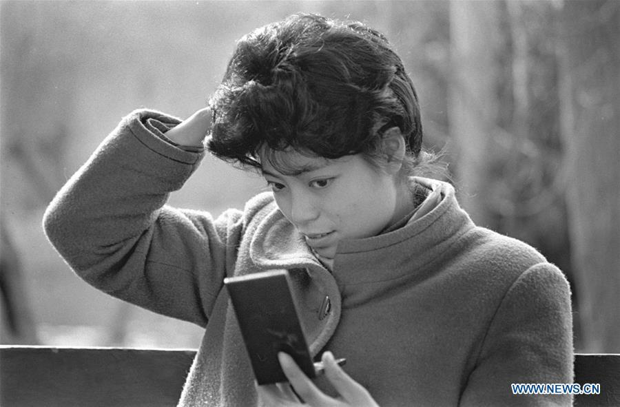A woman arranges her wig in the mirror in Chengdu, capital of southwest China\'s Sichuan Province, March 3, 1990. Along with China\'s reform and opening-up starting from 1978, Chinese women have refreshed their images year after year, which can be simply seen from their hairstyles. Women\'s hairstyles, just like a mirror, reflect fashion changes and most importantly, Chinese women\'s increasingly diversified definition of beauty. (Xinhua/Chen Xie)
