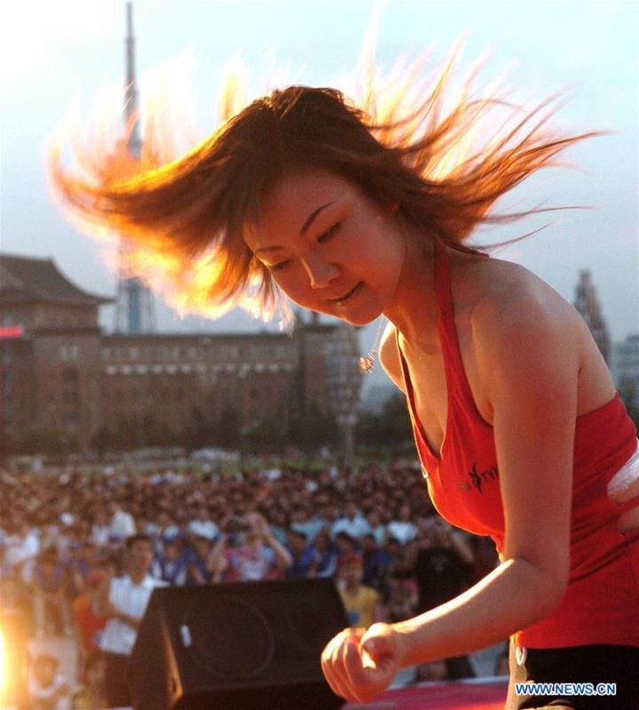 A girl flings her hair during a hip hop competition at a square in Changchun, capital of northeast China\'s Jilin Province, June 6, 2004. Along with China\'s reform and opening-up starting from 1978, Chinese women have refreshed their images year after year, which can be simply seen from their hairstyles. Women\'s hairstyles, just like a mirror, reflect fashion changes and most importantly, Chinese women\'s increasingly diversified definition of beauty. (Xinhua/Xu Jiajun)