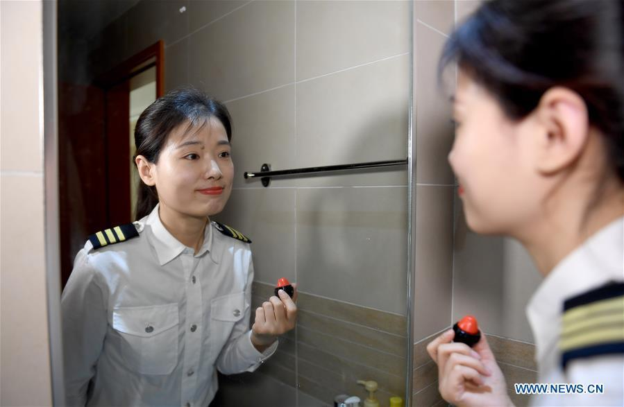 Jiang Dandan makes up before going to work in Yanliang District of Xi\'an, capital of northwest China\'s Shaanxi Province, on March 5, 2019. Jiang Dandan, 29, is one of the youngest test pilots in China and the only female test pilot for commercial transport aircrafts currently being trained at the Aviation Industry Corporation of China, Ltd. She went through dozens of professional courses and 750 hours of flying practice in six years. At the end of 2017, she became a test pilot and participated in the test flights during the research and development of ARJ21-700, C919 and other types of aircrafts. (Xinhua/Liu Xiao)