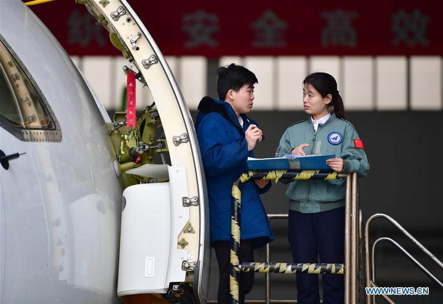 Jiang Dandan (R) discusses flight-test affairs with a crew member in Yanliang District of Xi\'an, capital of northwest China\'s Shaanxi Province, on March 5, 2019. Jiang Dandan, 29, is one of the youngest test pilots in China and the only female test pilot for commercial transport aircrafts currently being trained at the Aviation Industry Corporation of China, Ltd. She went through dozens of professional courses and 750 hours of flying practice in six years. At the end of 2017, she became a test pilot and participated in the test flights during the research and development of ARJ21-700, C919 and other types of aircrafts. (Xinhua/Shao Rui)