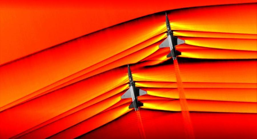 Using the schlieren photography technique, NASA was able to capture the first air-to-air images of the interaction of shockwaves from two supersonic aircraft flying in formation. These two U.S. Air Force Test Pilot School T-38 aircraft are flying in formation, approximately 30 feet apart, at supersonic speeds, or faster than the speed of sound, producing shockwaves that are typically heard on the ground as a sonic boom. The images, originally monochromatic and shown here as colorized composite images, were captured during a supersonic flight series flown, in part, to better understand how shocks interact with aircraft plumes, as well as with each other. (Photo/NASA)