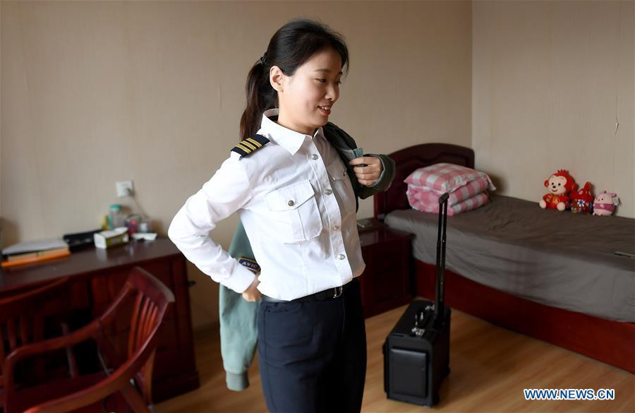 Jiang Dandan puts on clothes to go to work in Yanliang District of Xi\'an, capital city of northwest China\'s Shaanxi Province, on March 5, 2019. Jiang Dandan, 29, is one of the youngest test pilots in China and the only female test pilot for commercial transport aircrafts currently being trained at the Aviation Industry Corporation of China, Ltd. She went through dozens of professional courses and 750 hours of flying practice in six years. At the end of 2017, she became a test pilot and participated in the test flights during the research and development of ARJ21-700, C919 and other types of aircrafts. (Xinhua/Liu Xiao)