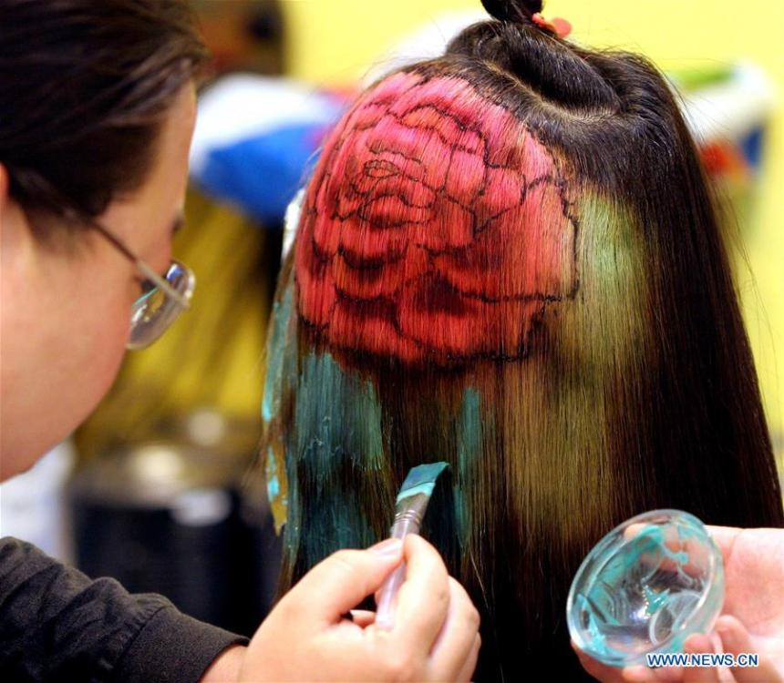 A hairdresser applies dye to a model\'s hair in Luoyang, central China\'s Henan Province, April 30, 2005. Along with China\'s reform and opening-up starting from 1978, Chinese women have refreshed their images year after year, which can be simply seen from their hairstyles. Women\'s hairstyles, just like a mirror, reflect fashion changes and most importantly, Chinese women\'s increasingly diversified definition of beauty. (Xinhua/Zhang Xiaoli)