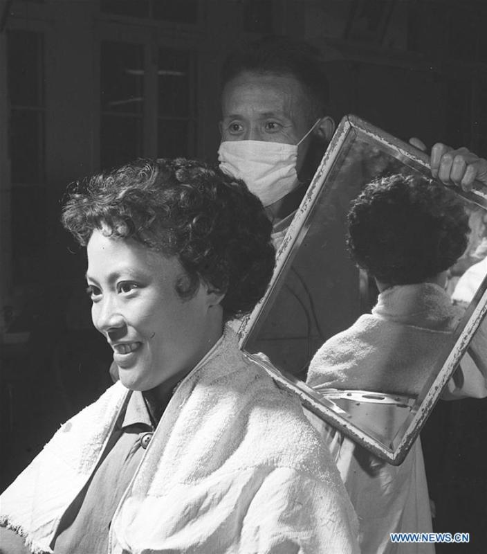 A woman looks into a mirror at a barber shop in Xidan of Beijing, capital of China, Nov. 10, 1959. Along with China\'s reform and opening-up starting from 1978, Chinese women have refreshed their images year after year, which can be simply seen from their hairstyles. Women\'s hairstyles, just like a mirror, reflect fashion changes and most importantly, Chinese women\'s increasingly diversified definition of beauty. (Xinhua/An Kang)