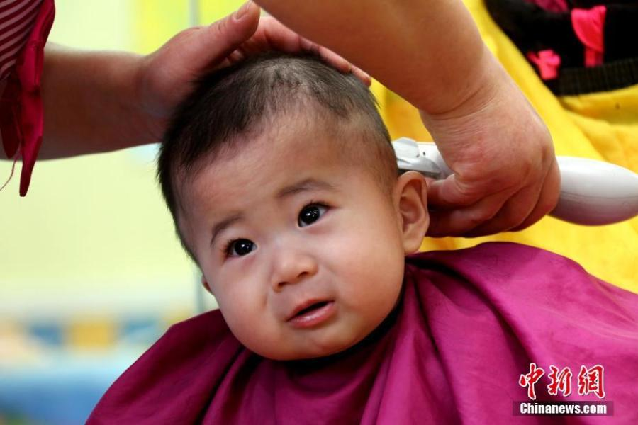 A child gets a haircut in Zaozhuang City, Shandong Province, March 8, 2019. March 8 marks traditional Chinese festival Long Tai Tou (dragon head raising), which refers to the start of spring and farming. During the festival, held on the second day of the second month of the lunar calendar, people play dragon lanterns, eat noodles, shave their hair, and pray for luck. (Photo: China News Service/Ji Zhe)