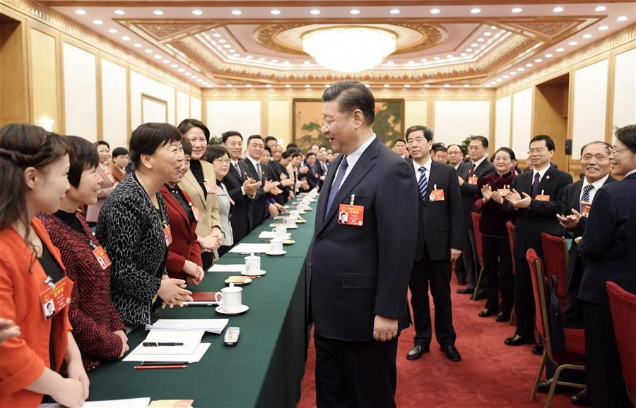 Chinese President Xi Jinping, also general secretary of the Communist Party of China (CPC) Central Committee and chairman of the Central Military Commission, talks with female deputies when joining deliberation with deputies from central China\'s Henan Province at the second session of the 13th National People\'s Congress in Beijing, capital of China, March 8, 2019. Xi extended greetings and best wishes to female lawmakers, political advisors and staff workers at the ongoing \