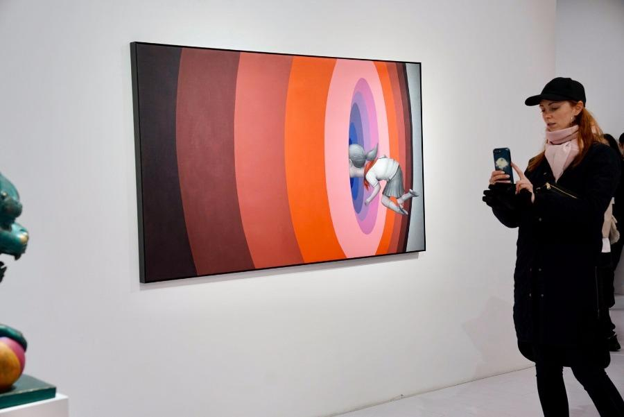 Visitors take photos of the artworks at the exhibition.(Photo/chinadaily.com.cn)  Born in Paris in 1972, Malland rose to fame in Shanghai with his paintings of children on the walls in different parts of the city.  He started painting on walls in the mid-1990s and has since 2003 been touring the world to interact with street artists from different cultures.