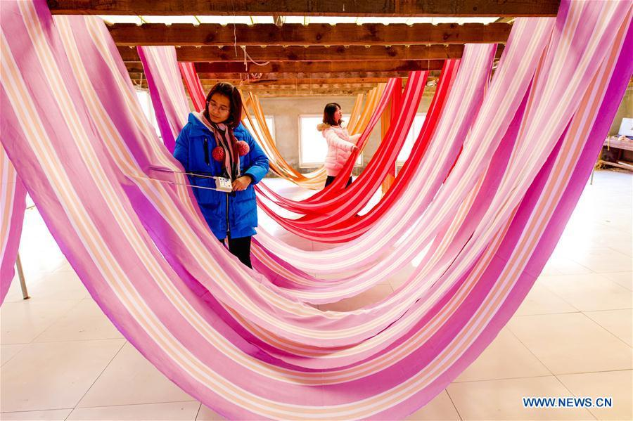 Women work at a cloth workshop in Jizhou District of Hengshui, north China\'s Hebei Province, Dec. 25, 2018. China\'s efforts and success in poverty reduction can help other developing nations, said experts observing the country\'s ongoing Two Sessions. The Two Sessions refer to the annual gatherings of the National People\'s Congress (NPC) and the National Committee of the Chinese People\'s Political Consultative Conference, China\'s top legislature and political advisory body respectively. China has emerged as a global role model with efforts in structural transformation and industrial upgrading, lifting hundreds of millions of people out of poverty, said retired Lieutenant Colonel Muhammad Faruk Khan, a presidium member of Bangladesh\'s ruling Awami League. (Xinhua/Li Xiaoguo)