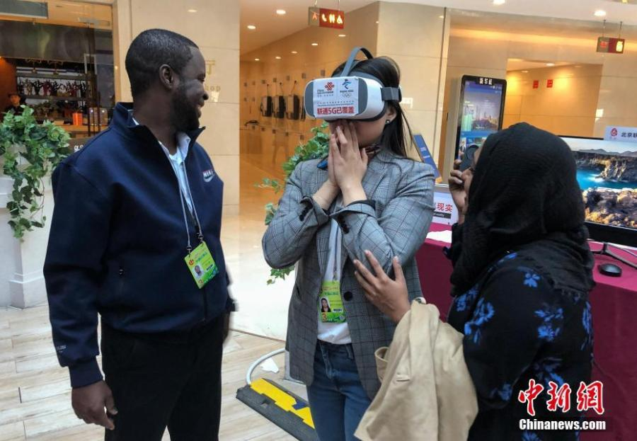 Mongolian journalist Enkhtur Anudari (M) experiences a 5G network device at the media center of the Two Sessions in Beijing\'s Media Center Hotel, March 11, 2019. (Photo: Cui Nan/China News Service)