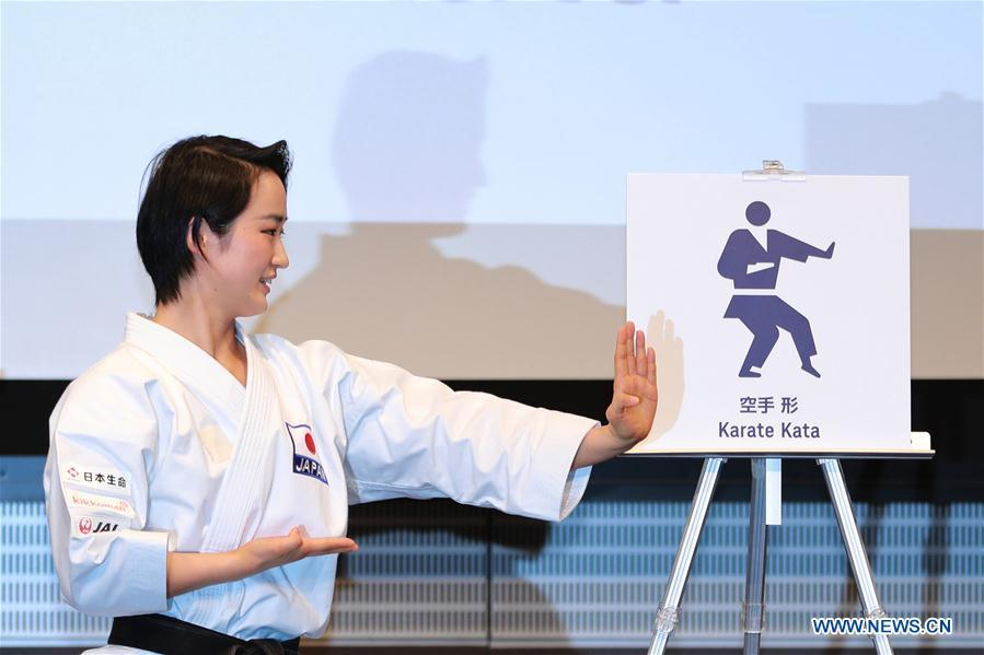 Japanese karate athlete Kiyo Shimizu takes the same action as the one Karate Kata pictogram shows at Tokyo 2020 Summer Olympic Games sport pictograms unveiling event in Tokyo, Japan, on March 12, 2019. (Xinhua/Du Xiaoyi)