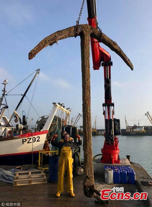 The fishing crew who netted the anchor from what might be the world\'s most valuable shipwreck display their find.  (Photo/VCG)