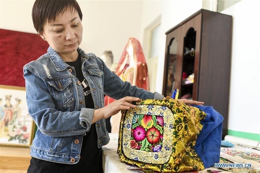 Renagul arranges her embroidery products at her workshop in Yizhou District of Hami City, northwest China\'s Xinjiang Uygur Autonomous Region, on March 8, 2019. The haute couture, literally named \