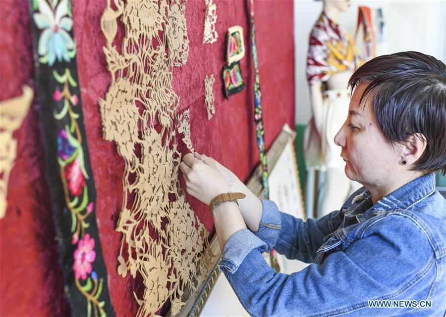 Renagul arranges papercuttings for sequins incorporated in the embroidery at her workshop in Yizhou District of Hami City, northwest China\'s Xinjiang Uygur Autonomous Region, on March 8, 2019. The haute couture, literally named \
