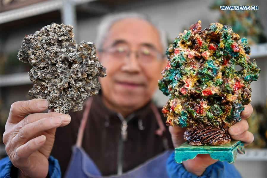 Ge Yuansheng, inheritor of coloured glaze firing skill, a national intangible cultural heritage listed in 2008, displays a piece of coal cinder (L) and a piece of coloured glaze made of coal cinder at his workshop in Taiyuan, north China\'s Shanxi Province, March 13, 2019. Ge has been applying his skill of coloured glaze firing to waste coal cinder for five years. After going through dozens of processes, the waste material would be made into delicate artwork. (Xinhua/Cao Yang)