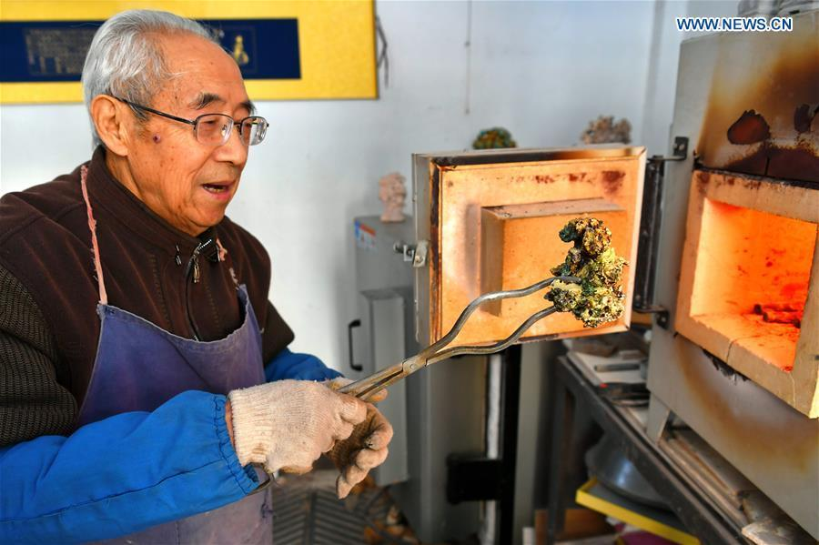 Ge Yuansheng, inheritor of coloured glaze firing skill, a national intangible cultural heritage listed in 2008, works on a piece of coloured glaze made of coal cinder at his workshop in Taiyuan, north China\'s Shanxi Province, March 13, 2019. Ge has been applying his skill of coloured glaze firing to waste coal cinder for five years. After going through dozens of processes, the waste material would be made into delicate artwork. (Xinhua/Cao Yang)