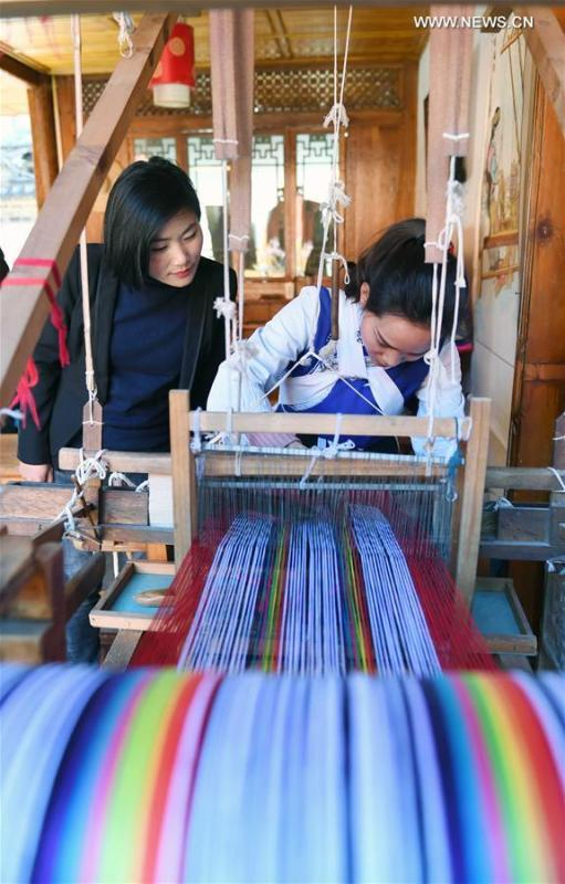 Fan Yongzhen (L), a deputy to the 13th National People\'s Congress (NPC), carries out a research on textile weaving skills of Naxi ethnic group in Lijiang ancient town, southwest China\'s Yunnan Province, Feb. 13, 2019.