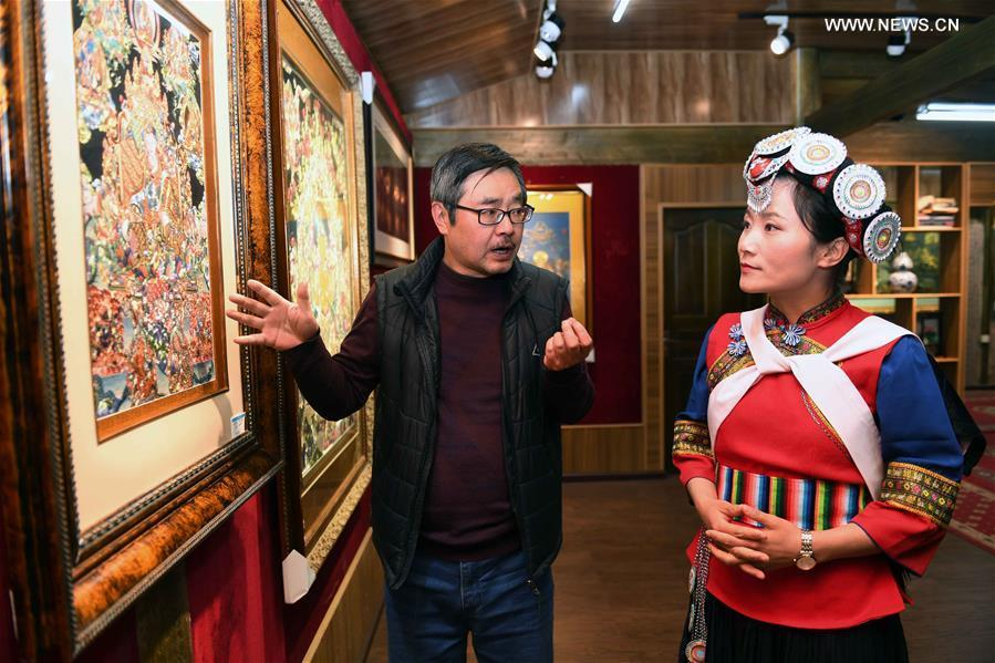 Fan Yongzhen (R), a deputy to the 13th National People\'s Congress (NPC), carries out a research on Thangka painting with dianxiu embroidery at Baisha Old Town of Yulong Naxi Autonomous County in Lijiang, southwest China\'s Yunnan Province, Feb. 13, 2019. (Xinhua/Yang Zongyou)