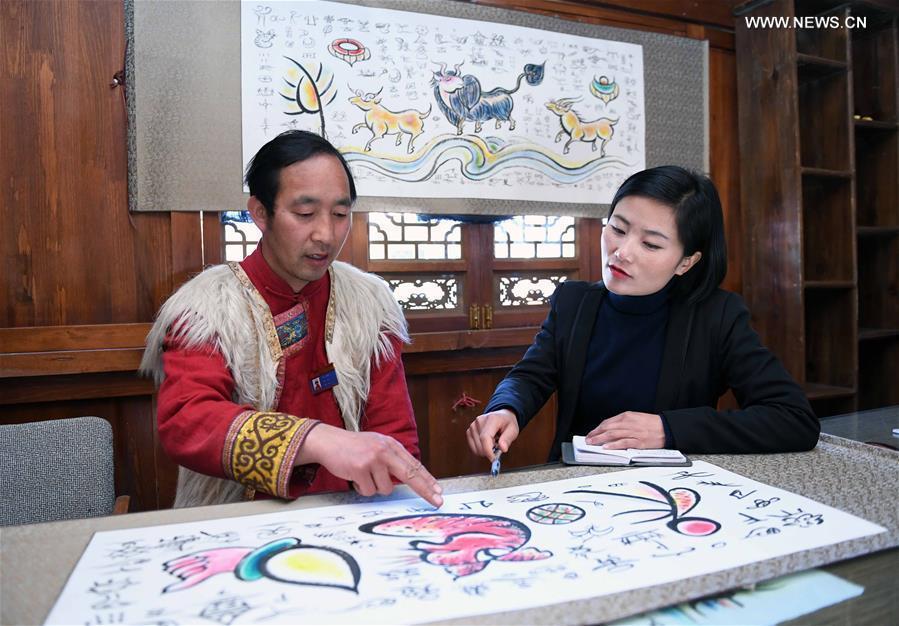Fan Yongzhen (R), a deputy to the 13th National People\'s Congress (NPC), carries out a research on the Dongba pictographic language at Yushuizhai Village of Yulong Naxi Autonomous County in Lijiang, southwest China\'s Yunnan Province, Feb. 13, 2019. (Xinhua/Yang Zongyou)
