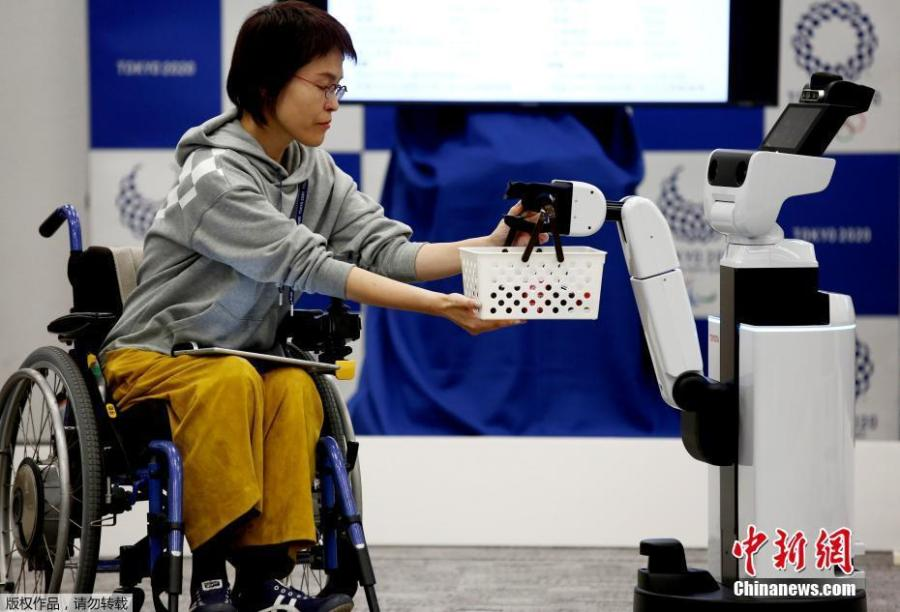Toyota\'s Human Support Robot (HSR) delivers a basket to a woman in a wheelchair at a demonstration of Tokyo 2020 Robot Project for Tokyo 2020 Olympic Games in Tokyo, Japan, March 15, 2019. (Photo/Agencies)