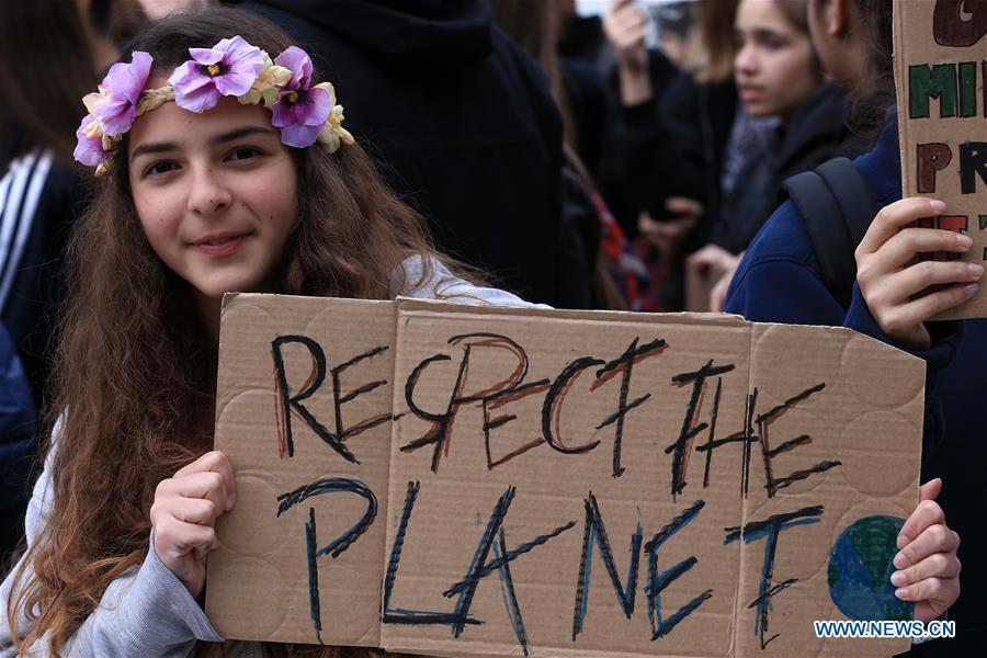A girl holds a placard in a march against climate change at Syntagma square, in Athens, Greece, March 15, 2019. (Xinhua/Marios Lolos)