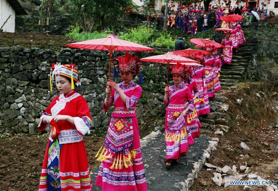 The bride is escorted by female friends to the bridegroom\'s home at a wedding ceremony in Mianhua Village of Siba Township of Luocheng Mulao Autonomous County, south China\'s Guangxi Zhuang Autonomous Region, March 17, 2019. A traditional wedding ceremony of the Mulao ethnic group is held here on Sunday. (Xinhua/Meng Zengshi)