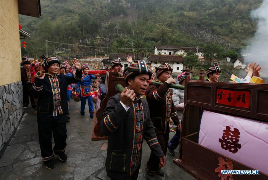 A team send dowries to the bridegroom\'s home at a wedding ceremony in Mianhua Village of Siba Township of Luocheng Mulao Autonomous County, south China\'s Guangxi Zhuang Autonomous Region, March 17, 2019. A tradit