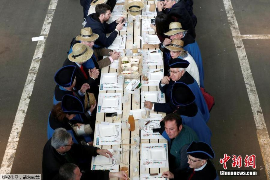 Participants attend a lunch served on a 401.22-meter-long table in the fruit and vegetable pavilion at the Rungis International Food Market during an event near Paris, France on March 17 celebrating the market's 50th anniversary, which also aims to set a Guinness World Record.(Photo/Agencies)