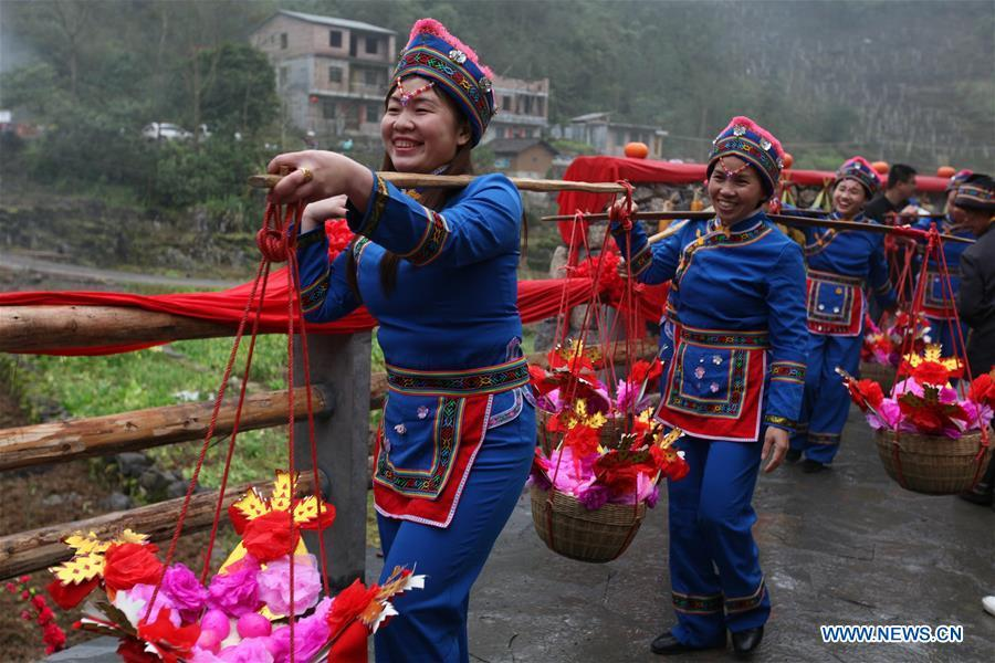 A team send dowries to the bridegroom\'s home at a wedding ceremony in Mianhua Village of Siba Township of Luocheng Mulao Autonomous County, south China\'s Guangxi Zhuang Autonomous Region, March 17, 2019. A traditional wedding ceremony of the Mulao ethnic group is held here on Sunday. (Xinhua/Meng Zengshi)