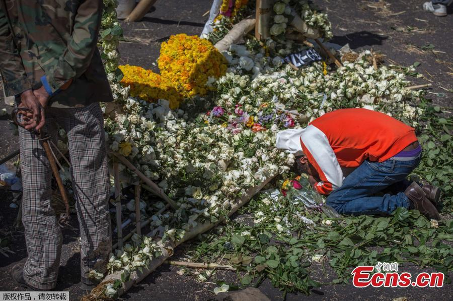A relative of the crashed Ethiopian jet victim mourns and grieves next to a floral tribute at the scene where the Ethiopian Airlines Boeing 737 Max 8 crashed shortly after takeoff killing all 157 on board, near Bishoftu, south-east of Addis Ababa, in Ethiopia Friday, March 15, 2019. (Photo/Agencies)