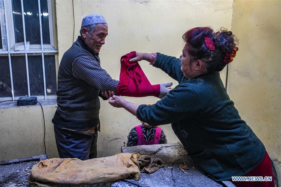 A woman helps her husband wrap a towel around his arm as a preparation before baking \