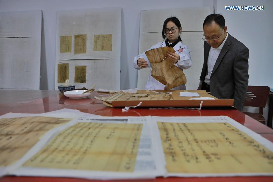 Wang Zongxun (R), curator of a museum of Jinping Writs, guides staff workers in regulating the documents at the museum in Jinping County, southwest China\'s Guizhou Province, March 18, 2019. Dating back to the Ming Dynasty (1368-1644), \