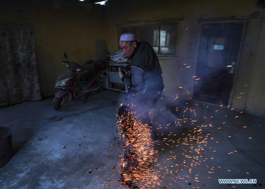 A baker deals with wood fire taken out of an oven at Daxi Village of Yuli County, northwest China\'s Xinjiang Uygur Autonomous Region, Jan. 29, 2019. Daxi Village is famous for its \