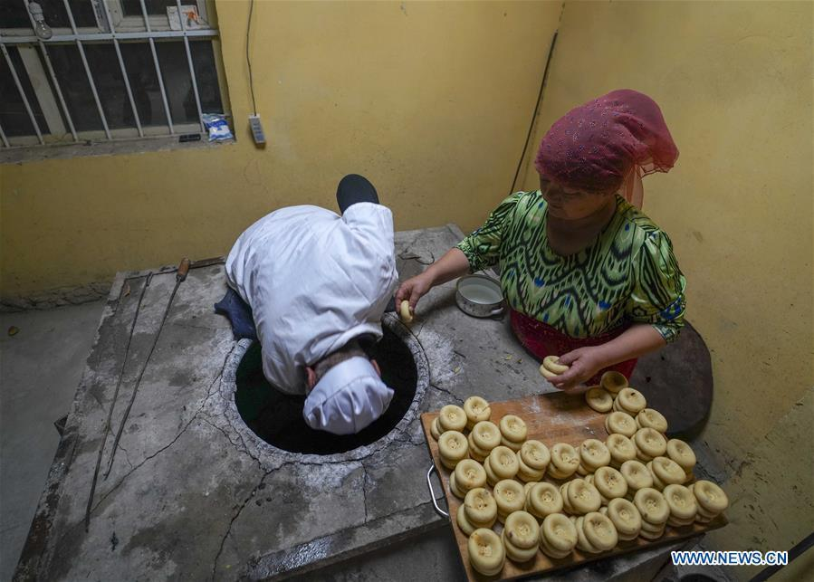 A woman helps her husband put doughs of \