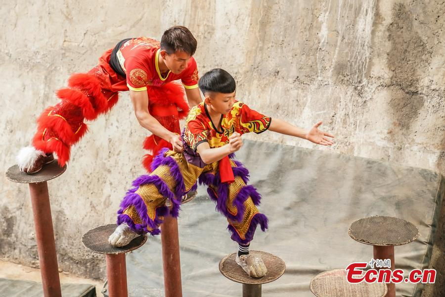 Tang Yifeng (L), a sixth grader, learns about lion dance in Tengxian County, Wuzhou City, South China\'s Guangxi Zhuang Autonomous Region, March 18, 2019. Tengxian is home to a special folk lion dance. The dance troupe, which formed in 1997, has won many top awards in contests, and its unique stunts that imitate a drunken lion or a lion climbing a cliff, for example, are particularly mind-blowing. (Photo: China News Service/Chen Guanyan)