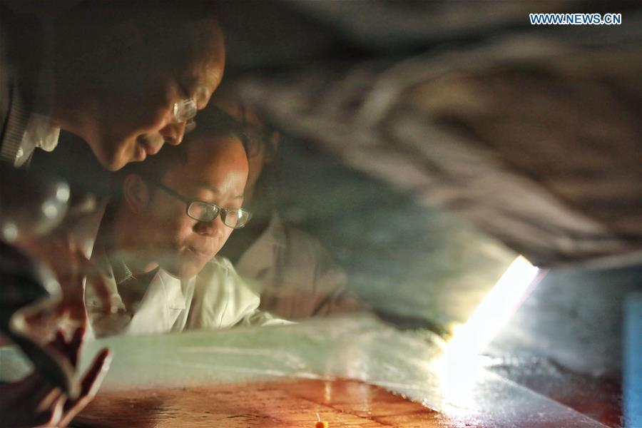 Wang Zongxun (L), curator of a museum of Jinping Writs, guides as a staff worker restores a document at the museum in Jinping County, southwest China\'s Guizhou Province, March 18, 2019. Dating back to the Ming Dynasty (1368-1644), \