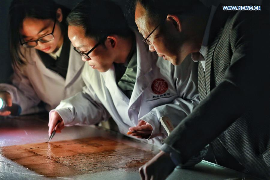 Wang Zongxun (R), curator of a museum of Jinping Writs, guides as staff workers restore a document at the museum in Jinping County, southwest China\'s Guizhou Province, March 18, 2019. Dating back to the Ming Dynasty (1368-1644), \