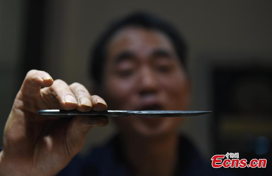 Craftsman Ding Jican makes Zhang Xiaoquan scissors using traditional methods in Hangzhou City, East China\'s Zhejiang Province, March 18, 2019. Zhang Xiaoquan scissors are a famous brand with a long history in China, and Ding has been committed to making the household utensil for 40 years. Ding himself is a master of the Zhang Xiaoquan scissor-making techniques, which have been perfected over the centuries and are recognized in China as a state intangible cultural heritage. (Photo: China News Service/Wang Gang)