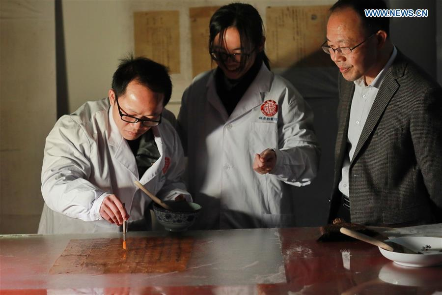 Wang Zongxun (R), curator of a museum of Jinping Writs, looks on as staff workers conduct paper-pasting on a document at the museum in Jinping County, southwest China\'s Guizhou Province, March 18, 2019. Dating back to the Ming Dynasty (1368-1644), \