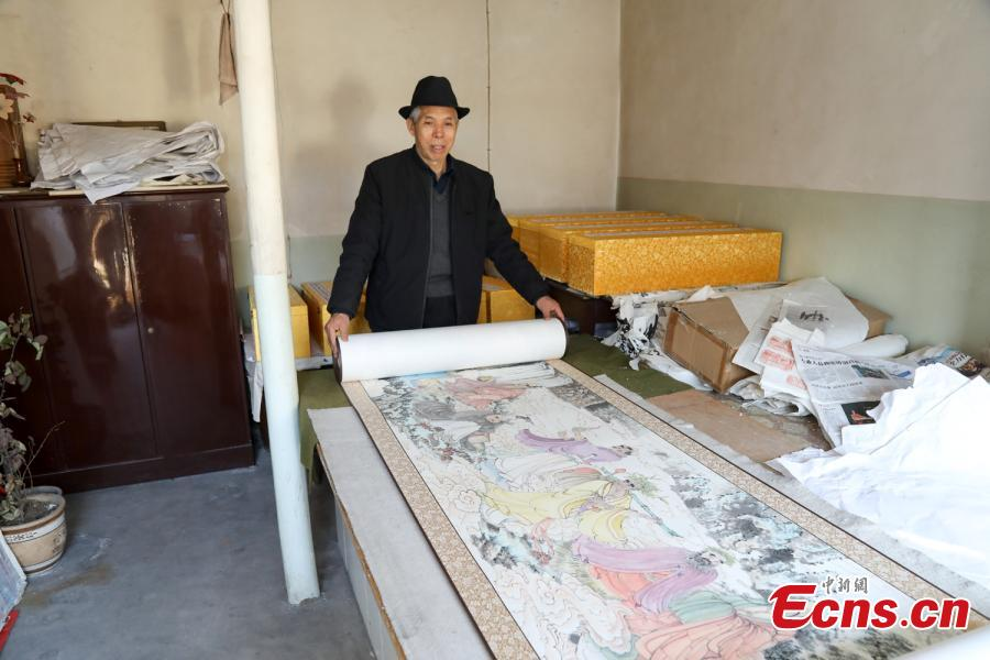 Zhang Zhanping shows his scrolls featuring a Buddhist scripture about 1,250 Arhats, a perfected person who has achieved spiritual enlightenment, in Daixian County, Xinzhou City, North China\'s Shanxi Province, March 18, 2019. The 66-year-old farmer, also a local folk artist specializing in the making and painting of Buddhist sculptures, said he spent eight years creating nine scrolls, each weighing five kilograms and measuring 69 centimetres in width. The total length of the scrolls measured more than 300 meters. He also said he had attempted to apply for a Guinness World Record. (Photo: China News Service/Wang Bintian)
