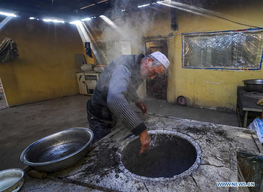 A baker sprays salty water into an oven before baking \
