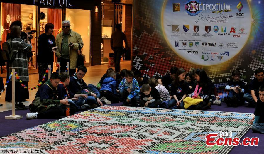 \'Bosnian qillim\' carpet made of plastic bottle caps in colors and patterns typical for Bosnian traditional wool carpet is displayed at Sarajevo City Center mall to mark the Global Recycling Day, March 18, 2019. The bottle cap carpet, made by 700 citizens of Sarajevo, covers 30 square meters of surface and was made using a total of 25,000 plastic bottle caps. (Photo/Agencies)