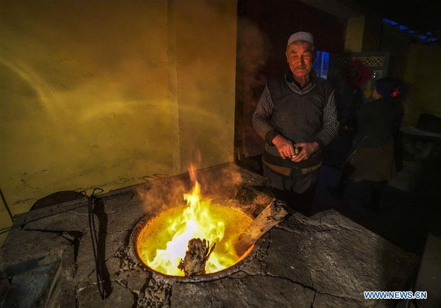 A baker checks the wood fire in an oven used to bake \