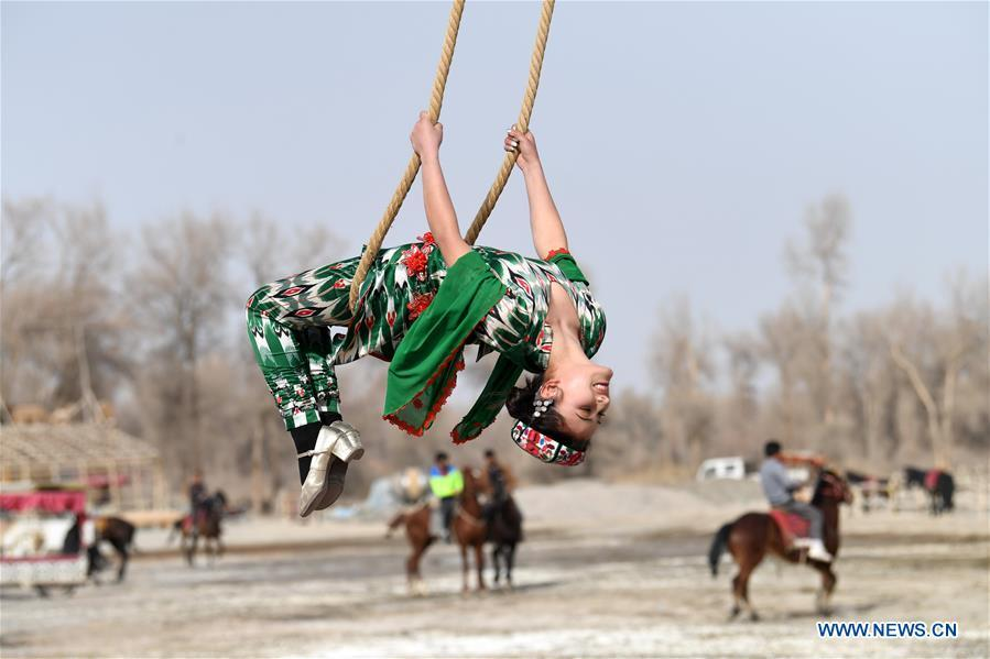 A girl participates in Shaghydi game in Daolang scenic spot of Awat County, northwest China\'s Xinjiang Uygur Autonomous Region, on March 12, 2019. Shaghydi is an ethnic sport game of Uygur people. Players push the bearings around to help people swing on ropes. (Xinhua/Sadat)