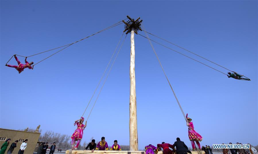 People participate in Shaghydi game in Daolang scenic spot of Awat County, northwest China\'s Xinjiang Uygur Autonomous Region, on March 12, 2019. Shaghydi is an ethnic sport game of Uygur people. Players push the bearings around to help people swing on ropes. (Xinhua/Sadat)